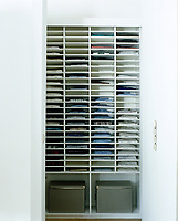 Single shirts are stored in narrow shelves in this regimented contemporary wardrobe