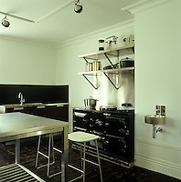 This contemporary black and white kitchen is furnished with a stainless steel table and high stools by Jasper Morrison