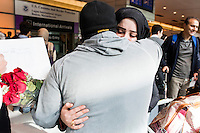 A couple who asked not to be identified embrace after the woman arrived in the US at Logan Airport's Terminal E in Boston, Massachusetts, USA..