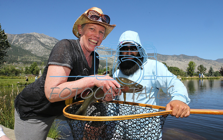 Breast cancer survivor Karen Kernan, of Reno, and her guide Jose Luna pose with her catch during a Casting for Recovery retreat in Gardnerville, Nev., on Friday, June 30, 2017. The nationwide program, hosted locally with Carson Tahoe Cancer Center, pairs cancer survivors with fly-fishing guides.   <br />