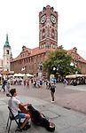 Toruń (województwo kujawsko-pomorskie) 22.07.2016. Uliczny muzyk na drugim planie Toruński Ratusz Staromiejski. To architektura gotycka światowej klasy, obecnie mieści się tam siedziba Muzeum Okręgowego.