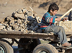 A boy drives a cart filled with rubble in Beit Lahia in the northern Gaza strip. Such rubble, the remains of buildings destroyed in Israeli airstrikes, is the main ingredient of new concrete blocks for reconstruction, and throughout Gaza thousands of children work collecting and transporting the material.