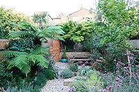 A lushly planted town garden that has an abundance of plants giving the garden a private and secluded feel. A wooden bench table is situated on a paved terrace at the end.