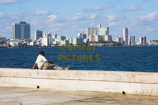 Man sitting on the sea wall, looking across to buildings and skyline of Havana city, Havana, Cuba