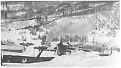 An east-facing hill side view showing a portion of the Rico yards with the water tank, a freight at the end of the depot and RGS #22 (2nd) doing switching duty on a snow clad day.<br /> RGS  Rico, CO