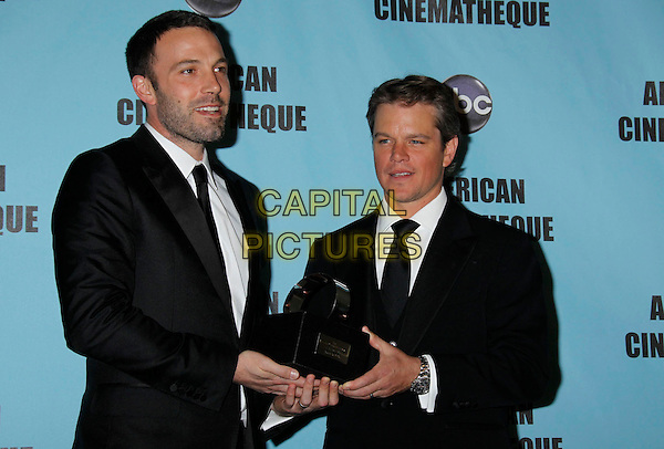 BEN AFFLECK & MATT DAMON .24th Annual American Cinematheque Award Presentation, held at the Beverly Hilton Hotel,  Beverly Hills, CA, USA, .27th March 2010 ..half length award trophy holding  black tie suit white shirt beard facial hair winner .CAP/ADM/MJ.©Michael Jade/Admedia/Capital Pictures