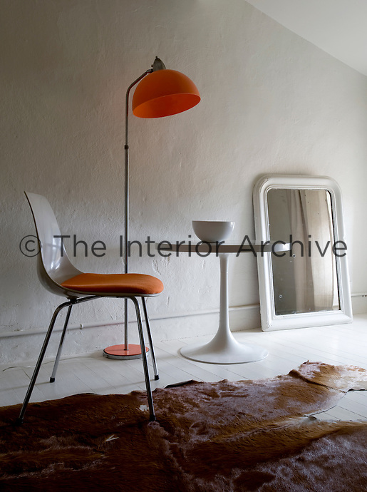 In the corner of a bedroom a standard lamp with an orange shade is placed between an orange and white chair and a Saarinen table