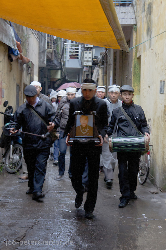 man carrying picture of the deceased family member on funeral procession with people wearing white headbands as symbol of death and mourning,streets of Hanoi, Vietnam