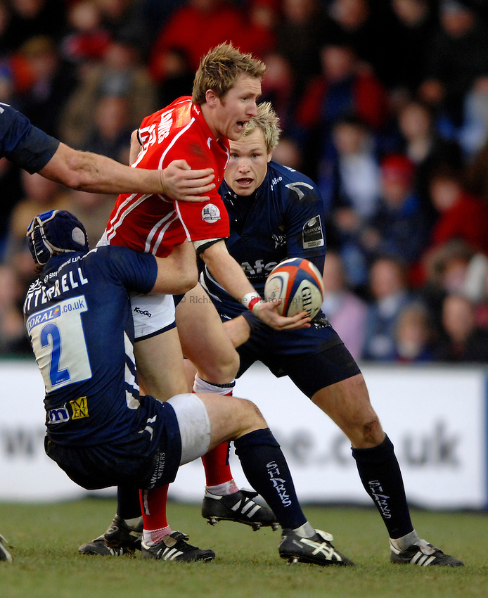 Photo: Richard Lane..Sale Sharks v Llanelli Scarlets. EDF Energy Anglo Welsh Cup. 02/12/2006. .Scarlets' Barry Davies passes as he is tackled by Sale's Andy Titterrell and Lee Thomas.