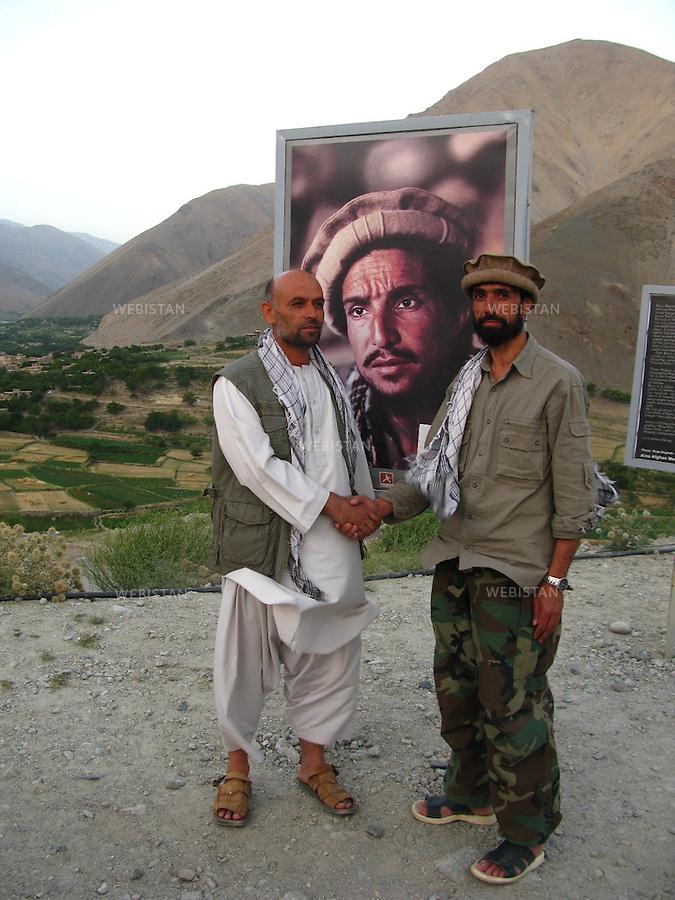 AFGHANISTAN - VALLEE DU PANJSHIR - 14 aout 2009 :.Exposition organisee par Reza sur le site du tombeau du commandant Massoud. Plus de cinquante photographies representant Massoud et ses hommes lors des guerres contre les russes puis les talibans etaient exposees autour des vestiges de tanks et de pieces d'artillerie russes pris par les moudjahidin lors de leurs assauts..Davoud, ancien garde du corps du Commandant Massoud et guide de Reza et Delazad Deghati pendant leur voyage, serrant la main d'un des gardiens du tombeau de Massoud, devant un portrait de ce dernier. ..2511.AFGHANISTAN - PANJSHIR VALLEY - August 14th, 2009: Exhibition organized by Reza at the site of Commander Massoud's tomb..More than fifty photographs of Massoud and his men taken during their fights against the Russians and the Taliban were exhibited amongst the vestiges of Soviet tanks and artillery seized by the mujahideen during their battles..Shaking hands in front of a portrait of Massoud: Dawoud Baraushah, Commander Massoud's former bodyguard and Reza and Delazad Deghati's guide in Afghanistan and one of the guardians of Massoud's tomb.
