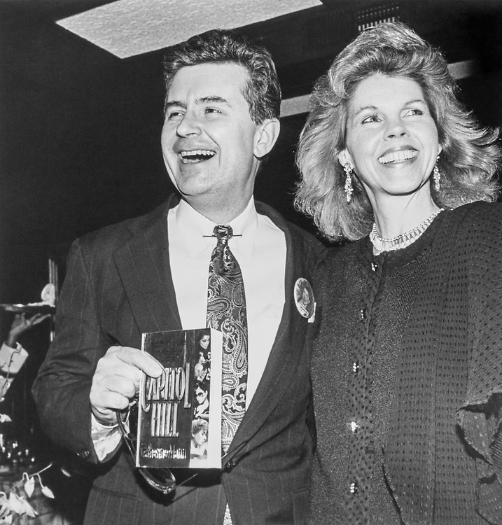 Rep. Fred Grandy R-Iowa holding wife's new book Capitol Hill and Catherine Mann smiling in 1992. (Photo by Laura Patterson/CQ Roll Call)