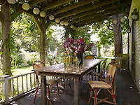 Bistro chairs surround a reclaimed wood table on the front porch