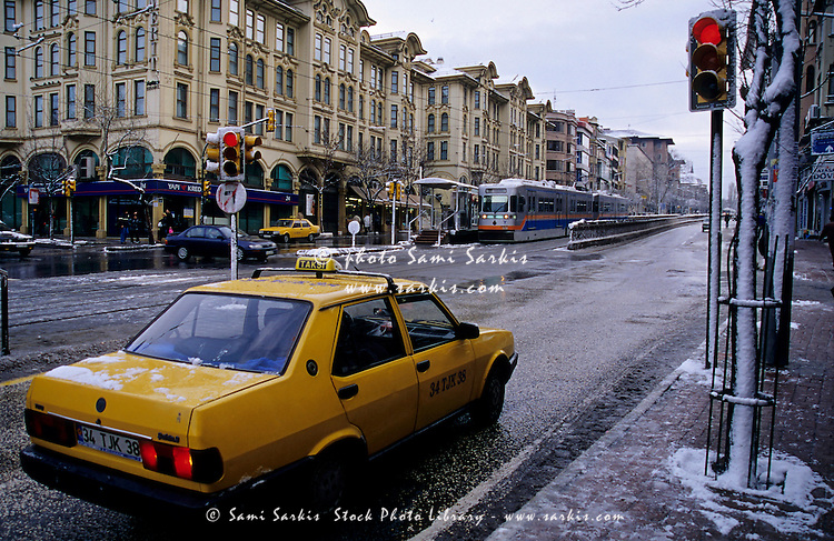 Yellow taxi stopped at a red light during winter in Istanbul, Turkey.