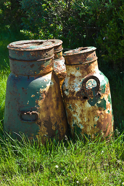 Old rusty galvanised iron milk creamery churns in County Clare, West of Ireland