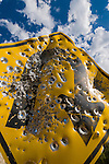 Bullet riddled yellow diamond traffic sign along a mountain road on the west slope of the Wasatch Plateau, clouds