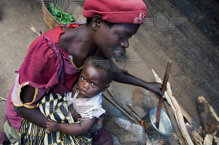 Eunice Chingoma holds her baby Hannah as she makes phala (maize porridge).