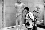 A woman knocks on a ancient statue to check if it is stone or wood. New York 1969. USA Its stone. .