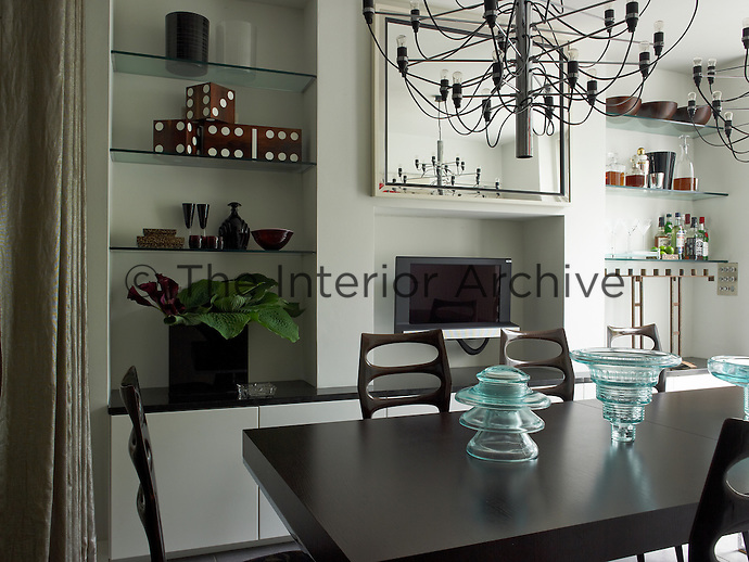 In the dining room an elegant table and chairs in dark polished wood contrasts with the pale chalky white walls