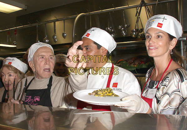 ANNE & KIRK DOUGLAS, LA Mayor ANTONIO VILLARAIGOSA & CINDY CRAWFORD.L.A. Mission and Anne Douglas Center's Thanksgiving Meal For The Homeless held at The Los Angeles Mission, Los Angeles, California, USA..November 26th, 2008.half length red apron white silk satin pattern top hat paper plates food feeding latex gloves hand pointing mouth open married husband wife .CAP/ADM/KB.©Kevan Brooks/AdMedia/Capital Pictures.
