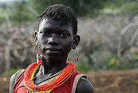 UGANDA Karamoja, village Nakapelimoru of Jhi tribe of Karimojong, young woman with facial ornament / UGANDA Karamoja , Volk der Karimojong , Dorf Nakapelimoru  der Jhi,  junge Frau mit Gesichtsverzierung und Schmuck aus Autoblinklicht