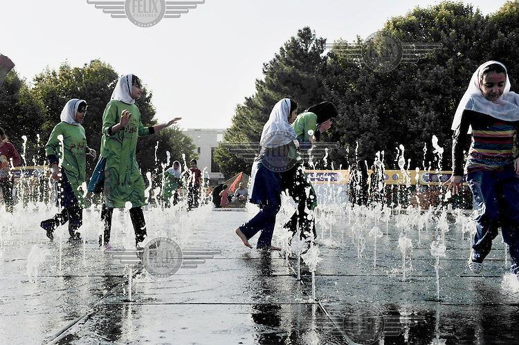 Teenage Girls playing among water fountains in a park.