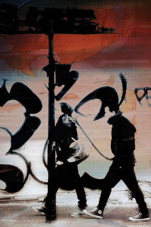 A young couple walks in the Arab quarter Barbes in Paris and passes Graffiti.