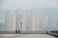 A Man And A Woman On A Pedestrian Area Overlooking The Sunshine 100 New City Commercial Real Estate Development In Chongqing, China.  © LAN