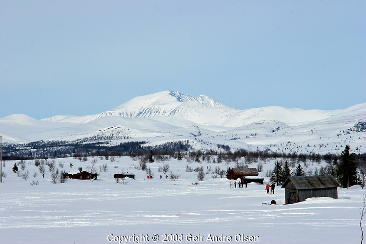 Storrondan in Rondane National Park in the background, skiiers enjoying the beautyfull Norwegian winters day