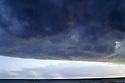 Cumulonimbus cloud building up over coast producing showers. Subtropical Queensland near border of NSW