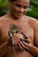 Valdinei da Conceção Cardoso mostra o filhote de cotia capturado nas matas da região.<br /> Rio Aurá.<br /> Belém, Pará, Brasil<br /> Foto Paulo Santos<br /> 19/03/2013