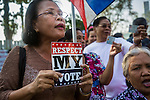 """01 FEBRUARY 2014 - BANGKOK, THAILAND: A Thai woman holds up a """"Respect My Vote"""" placard while she tries to go to her polling place in the Din Daeng area of Bangkok. Thais went to the polls in a """"snap election"""" Sunday called in December after Prime Minister Yingluck Shinawatra dissolved the parliament in the face of large anti-government protests in Bangkok. The anti-government opposition, led by the People's Democratic Reform Committee (PDRC), called for a boycott of the election and threatened to disrupt voting. Many polling places in Bangkok were closed by protestors who blocked access to the polls or distribution of ballots. The result of the election are likely to be contested in the Thai Constitutional Court and may be invalidated because there won't be quorum in the Thai parliament.    PHOTO BY JACK KURTZ"""