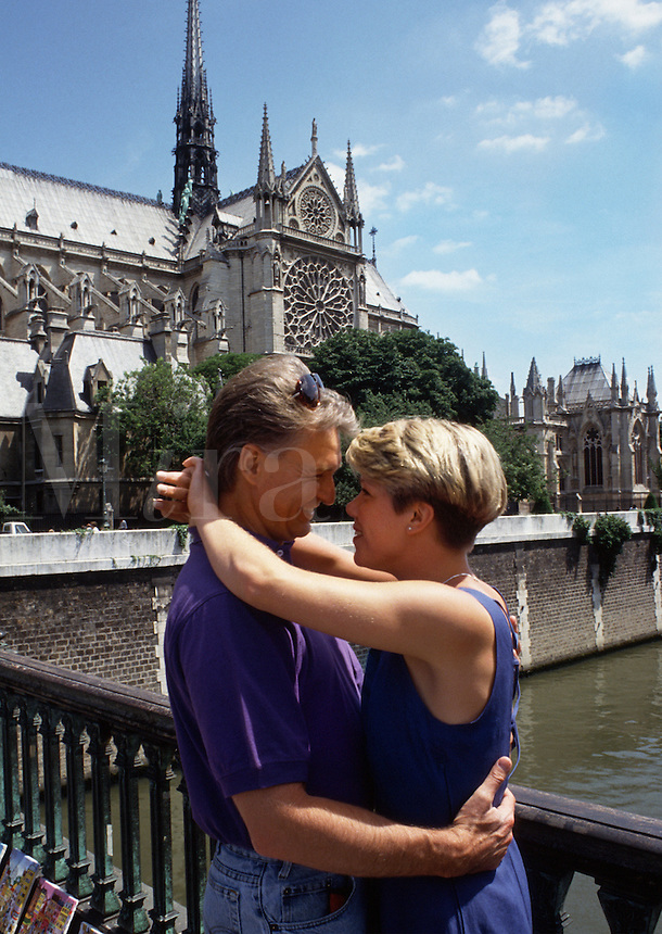 A smiling, romantic couple on vacation embraces on a bridge overlooking Notre Dame Cathedral.