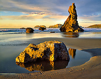 Low tide and sunset with volcanic stack rocks at Bandon beach. Oregon