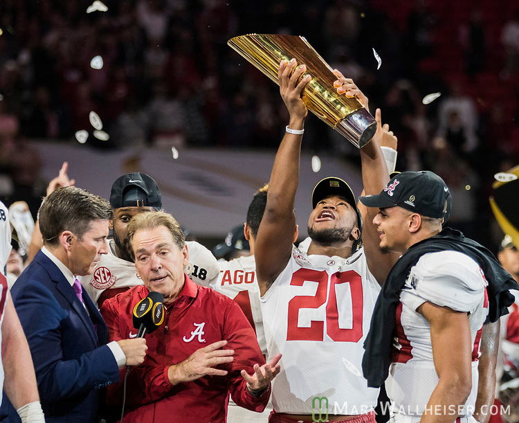 Alabama Crimson Tide linebacker Shaun Dion Hamilton (20) hoists the National Championship trophy while Alabama Crimson Tide head coach Nick Saban is being interviewed after defeating the Georgia Bulldogs 26-23 in the NCAA College Football Playoff National Championship at Mercedes-Benz Stadium on January 8, 2018 in Atlanta. Photo by Mark Wallheiser/UPI
