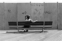 USA. New York City. A lonely man seats on a bench on the boardwalk in Coney Island. Graffiti on the wooden wall. No view. © 1986 Didier Ruef