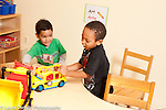 Education preschool 3 year olds two boys playing together with plastic truck and bus vocalizing making truck sounds horizontal