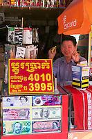 Phnom Penh, Cambodia. Central Market. Money changer and SIM card seller.