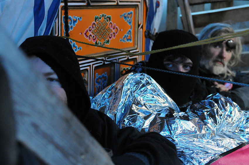 November 23, 2011, Toronto Police in significant numbers deployed during the predawn hours this morning, beginning the process of evicting the Occupy Toronto tent camp from St. James Park.  Here at first light of dawn, three unidentified protest supporters are chained and barricaded in at the library yurt awaiting the police.