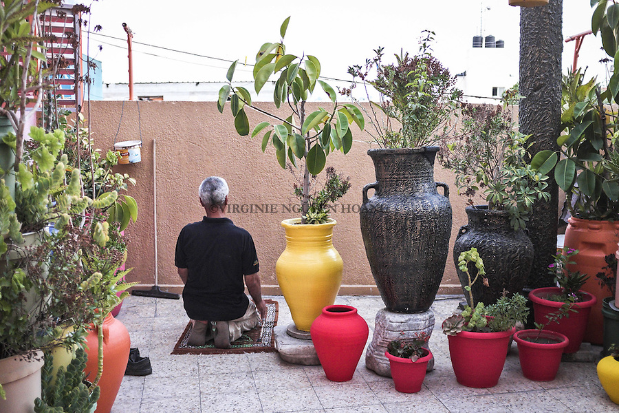 GAZA, Zaytoun: Mohammed Al Saedi is doing his prayer in the courtyard of his house. Around him the walls and flower pots painted by him. 15/08/15<br /> <br /> GAZA , Zaytoun : Mohammed Al Saedi fait sa pri&egrave;re dans la cour de son jardin. Autour de lui, les murs et pots de fleurs qu'il a peint. 15/08/15