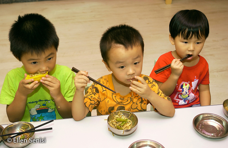 Beijing, China.Little Oak Children's House: private day care center and private elementary school..Three boys eat noodles and vegetables (some with chopsticks) at snack time..© Ellen B. Senisi
