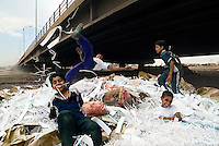 Baghdad, Iraq, June 4, 2003.Omar (flying) and his friends are working children, sorting garbage under an expressway bridge to earn a little extra money for their family.