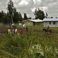 People pass in front of the Cholga Health Center in rural Ethiopia on August 24, 2010.