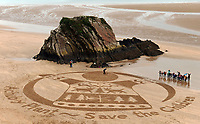 Pictured: A Save The Children artwork on the sandy beach of Tenby in Pembrokeshire, west Wales, UK.<br /> Re: A sand-art seasonal sweater is decorating Tenby's North Beach in west Wales, UK.<br /> The festive design, to mark Save the Children's Christmas Jumper Day, is the work of Pembrokeshire 'sand circles' artist Marc Treanor.<br /> He had a helping hand from local schoolchildren and volunteers to etch out his artwork.<br /> Marc was approached by the charity to create the jumpers on four Welsh beaches.<br /> He worked on the sands in Anglesey on Friday; Mwnt, near Cardigan yesterday (Sunday) and on Wednesday takes his talent to Barry Island's Whitmore Bay.