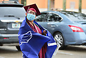 PEMBROKE PINES, FL - MAY 15: Student Jessica Chin wears a mask and the school flag during the graduation ceremony at Pembroke Pines Charter High School on May 15, 2020 in Pembroke Pines, Florida. Because of social distancing mandates instituted by the state to curtail the spread of COVID-19, the 2020 graduates received their diplomas in a near-empty auditorium with no friends, family or relatives allowed to attend. A video of each student walking the stage to receive their diploma will be streamed on the school's scheduled graduation date of May 29.   ( Photo by Johnny Louis / jlnphotography.com )