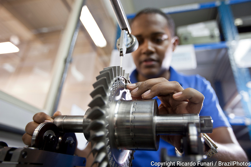 Young black factory worker, aerospace industry, machining and balancing sector, mechanic performing counting and measuring of parts, Brazil.