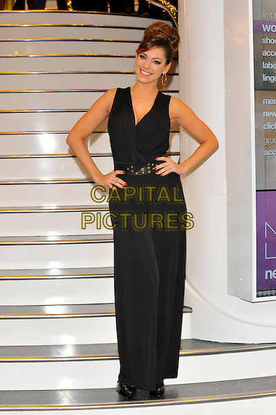 Kelly Brook.Opens New Look Store in Oxford Street, London, England, UK, .9th November 2012..full length black sleeveless hands on hips belt hair up bun hoop earrings photocall pantsuit catsuit jumpsuit .CAP/CJ.©Chris Joseph/Capital Pictures.