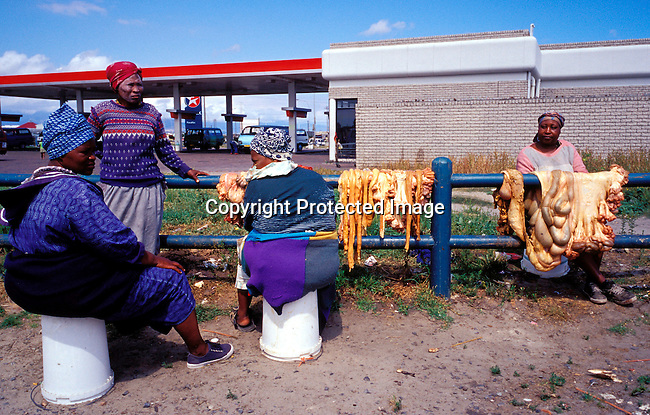 disbven00003.Digital. Small Business. Vendors. Women selling cow intestines close to Nonqubela train station on November 4, 2003 in Site C Khayelitsha, a township about 35 kilometers outside Cape Town, South Africa. It's popular for making traditional food. .©Per-Anders Pettersson/iAfrika Photos