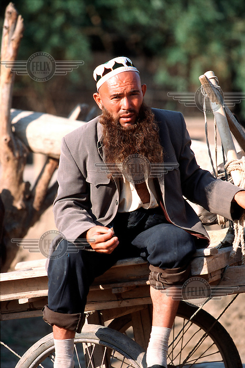 A Uighur trader sits on his cart in Kashgar market. Ethnically closer to the people of central Asia, the Uighurs share little culturally with the Han Chinese.