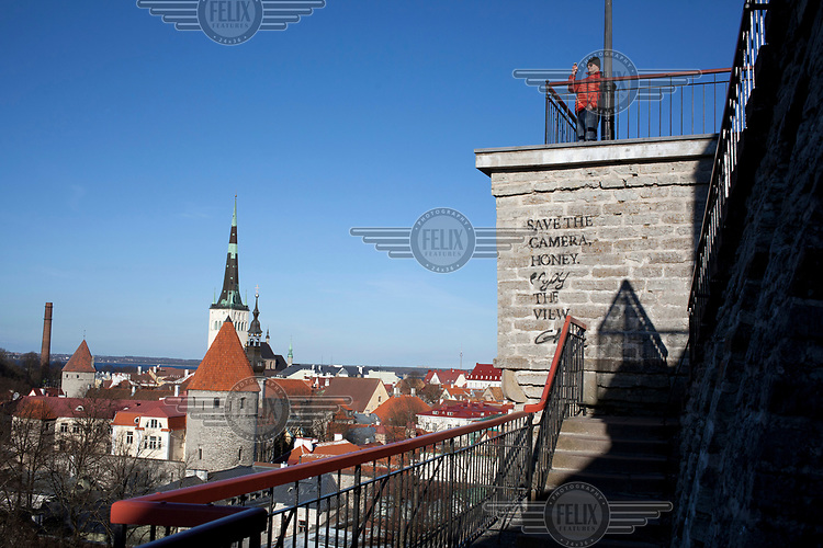 A man uses his smartphone while enjoying a vew of the old town.