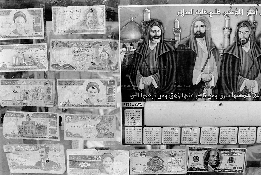 "Iraq. Kufa. 15 km from Najaf. Near the Muslem Bin Akel mosque, a money changer for pilgrims coming during the month of Muharram, considerated as one of the most important feast for the Shiism branch of Islam. The United States one hundred-dollar bill ($100) is a denomination of United States currency. U.S. statesman, inventor and diplomat Benjamin Franklin is currently featured on the bill. Iranian rial banknotes are the banknotes and the currency of Iran, a  banknote featuring the Grand Ayatollah Sayyed Ruhollah Musavi Khomeini who was an Iranian religious leader and politician. The dinar is the currency of Iraq, featuring Saddam Hussein. A calender with the drawings of Imam Ali, Imam Hussein and Imam Abbas. Muharram is a month of remembrance that is often considered synonymous with the event of Ashura. Ashura, which literally means the ""Tenth"" in Arabic, refers to the tenth day of Muharram. It is well-known because of historical significance and mourning for the martyrdom of Hussein ibn Ali, the grandson of Muhammad. Shi'a Muslims start the mourning from the 1st night of Muharram and continue for two months and eight days. However the last days are the most important since these were the days where Hussein and his family and followers were killed in the Battle of Karbala which took place on Muharram 10, in the year 61 of the Islamic calendar (October 10, 680). Muharam's month is considerated as one of the most important feast for the Shiism branch of Islam. Shia Islam is the second largest denomination of Islam. The followers of Shia Islam are called Shi'ites or Shias. 27.02.04 © 2004 Didier Ruef ."